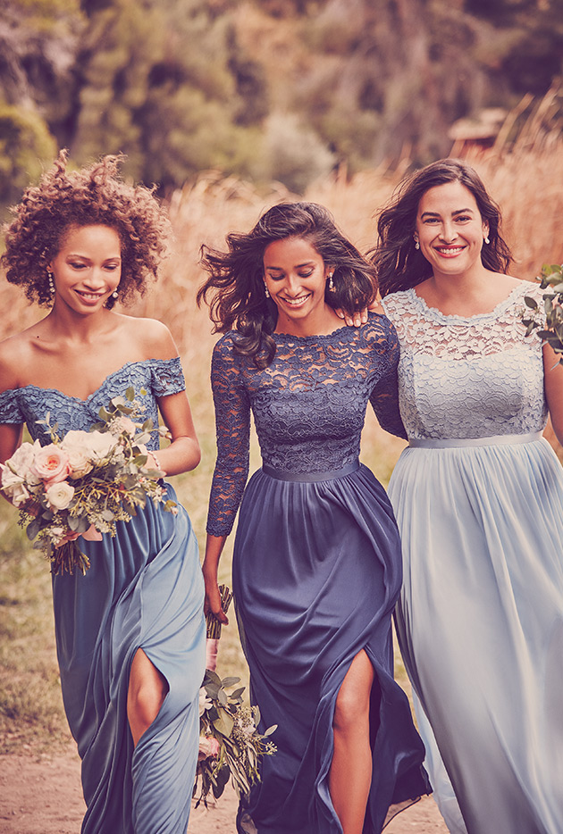 Three bridesmaids in lace dresses walking through field