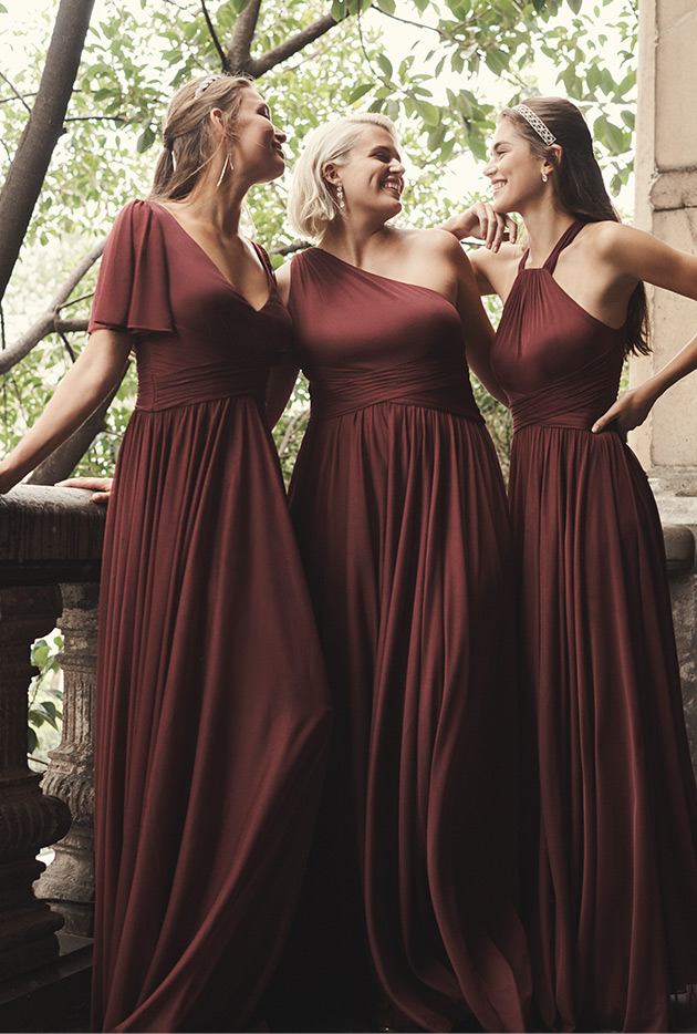 Three bridesmaids in wine dresses smiling at each other on a balcony