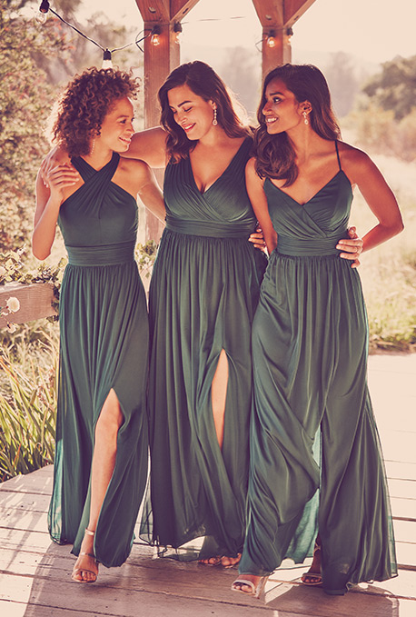 Three bridesmaids in green dresses walking with their arms around each other
