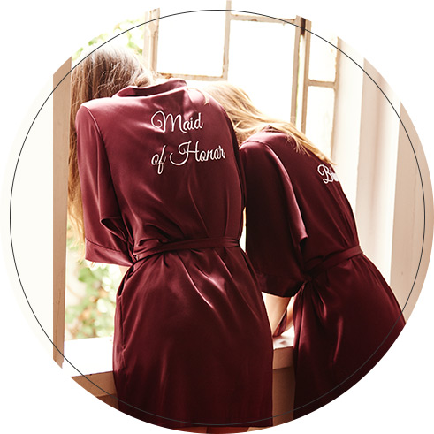 Bridesmaids in wine colored robes looking out a window with Maid of Honor written on the back