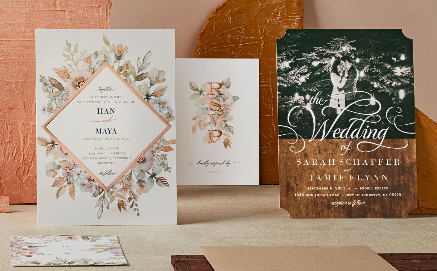 Personalized wedding invitations on wood table with floral details
