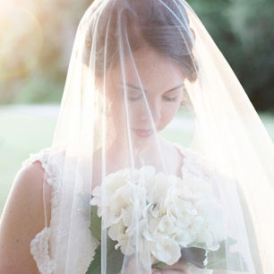 Bride wearing sheer veil with lace trim looking down at flower bouquet
