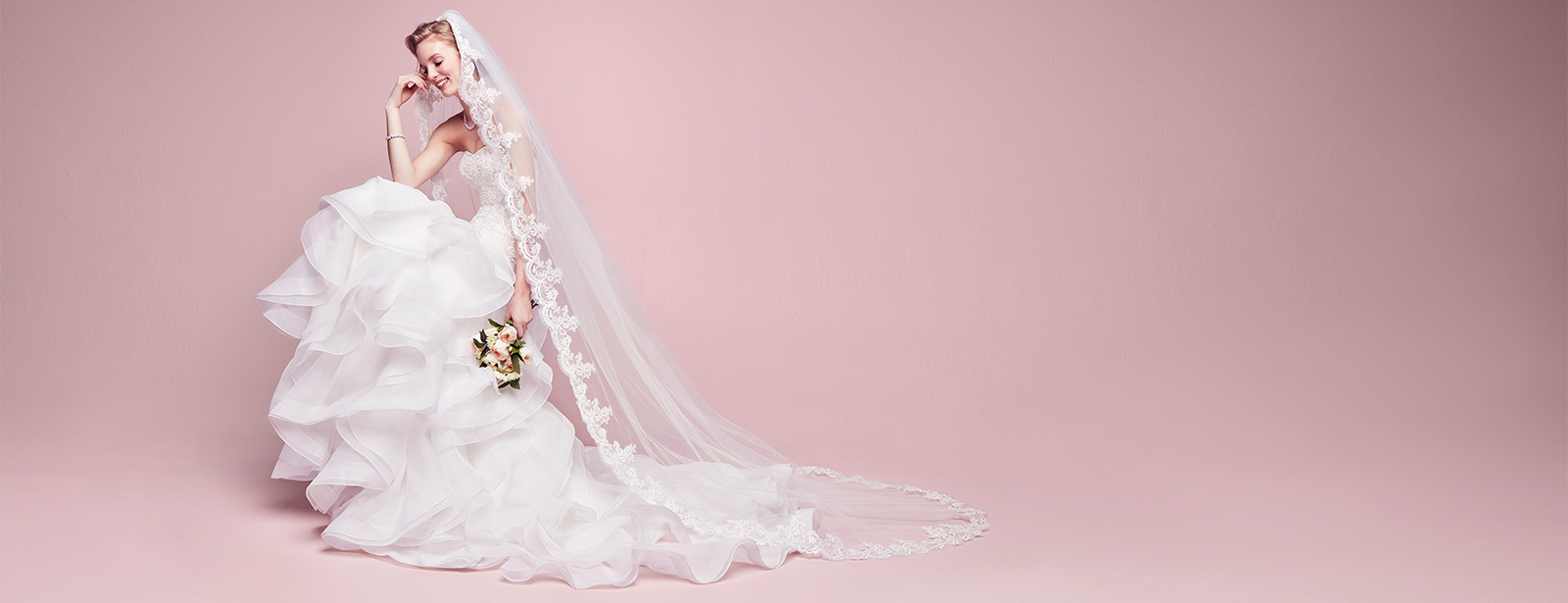 Seated bride wearing long veil with lace edging