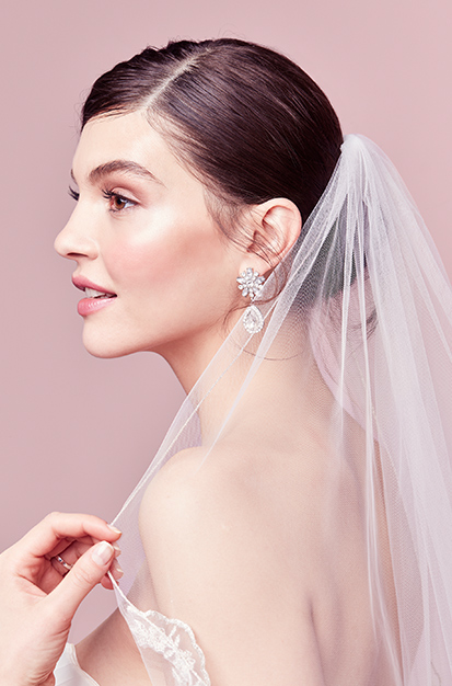 Bride wearing scrolled scallop-edge fingertip veil