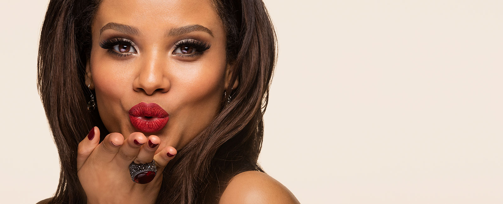 Woman blowing a kiss with red lipstick