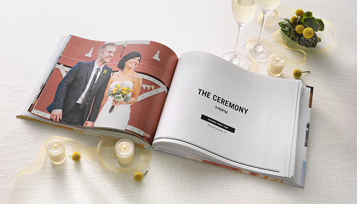 Professional wedding album surrounded by candles and champagne glasses