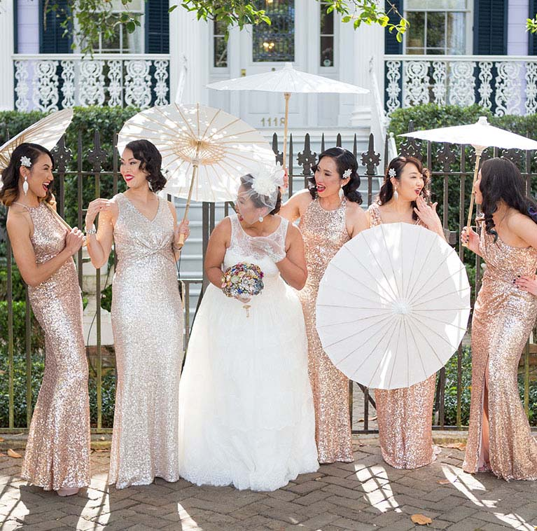 Bride and bridesmaids holding umbrellas laughing with one another